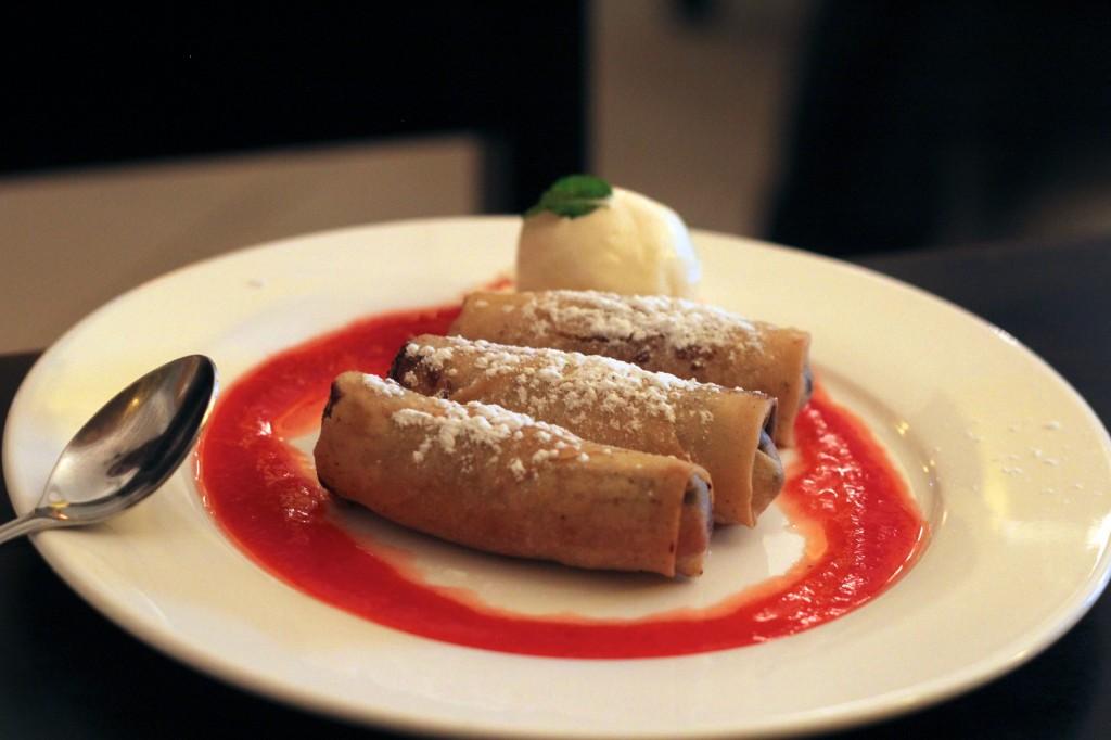 Nems fourrés à la banane et au chocolat sur leur lit de fruits rouges et accompagnés de sa boule de glace à la vanille
