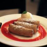 Nems fourrés à la banane et au chocolat sur leur lit de fruit rouge et accompagnés de sa boule de glace à la vanille