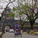 Cyclopousse devant une porte de la cité impériale à Hué